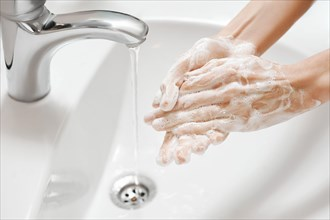 Hand Washing in white sink. Water flows from a faucet at soapy female hands. Covid-19 coronavirus protective measure.