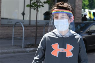 Boy wearing protective face masks and face shields during Covid-19 Pandemic in Montreal Canada (Model released)