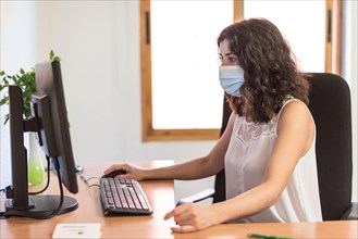 office worker in workplace. Covid -19 mask prevention. Working at pc and looking at screen