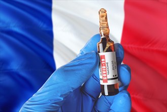 France flag with Coronavirus Covid-19 concept. Doctor with blue protection medical gloves holds a vaccine bottle. coronavirus covid 19 vaccine researc