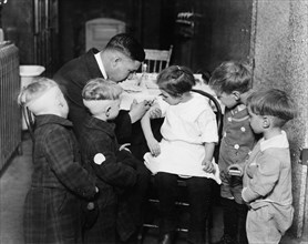 Pediatrician immunizing a little girl while other children are watching