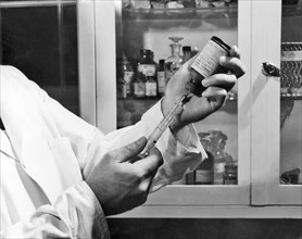 Centers for Disease Control (CDC) laboratorian filling a syringe with rabies vaccine, 1968. Image courtesy Centers for Disease Control. ()