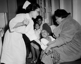 A nurse attempts to give a young child a flu shot in Chicago, ca.1962.