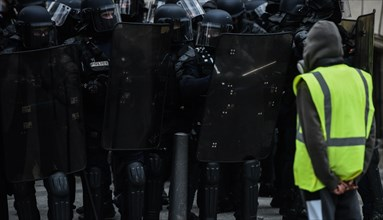 Paris, France - 8 December 2018: Yellow Vests (Gilets jaunes) protester stands in front of French riot police officers during a protests against livin