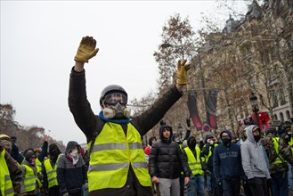 Champs-Elysees, Paris, France. 15th Dec 2018. Protestor wearing gas mask raises his hands to police. Yellow Vests (Gilets Jaunes) protests, Champs-Elysees, Paris, France, December 15, 2018. Credit: Ju...