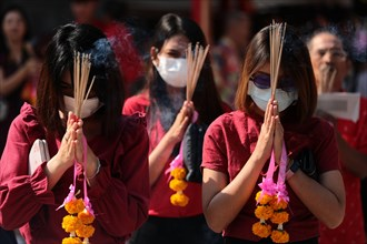 Women pray while wearing dust masks during the celebration at Leng Noei Yi Temple in Chinatown, Bangkok.The Lunar New Year, also known as Spring Festival in China marks the beginning of the Year of th...