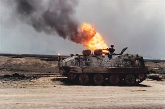 Kuwait City, Kuwait - April 1991 :  Damaged tank on road with burning oil fire from Persian Gulf War.