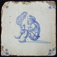 Tile with seated man with beret holding smoking tube or wooden trowel in the hand and or lighting or tapping, corner motif, ox
