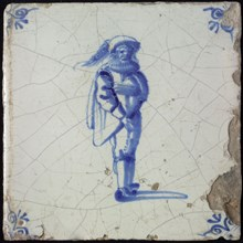Figure tile, blue with standing man with limp beret with plume, corner motif ox's head, wall tile tile sculpture ceramic