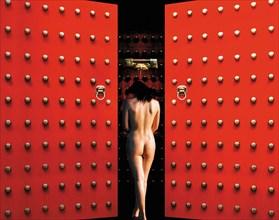 Femme nue de dos entre 2 battants de porte