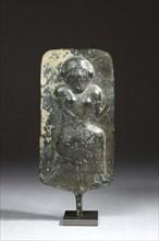 Plaque votive ornée au repoussé et ciselé d'une femme assise