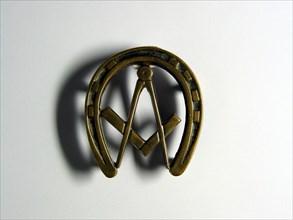 Repose plat en bronze en forme de fer à cheval, avec équerre et compas au centre