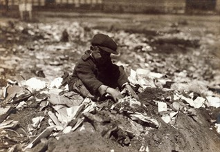 Photograph of a young scavenger going through the Trash on Pleasant Street dump