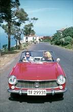 Femmes dans une Fiat rouge 1500 Spider