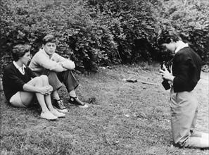 Jacqueline prenant en photo John F. Kennedy et l'une de ses soeurs.
