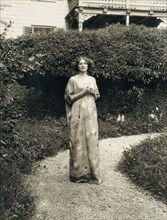 Emilie Floege in an artistic reform dress with floral pattern in the garden of the Oleander villa in Kammer at the Attersee lake. Photography, 1910.