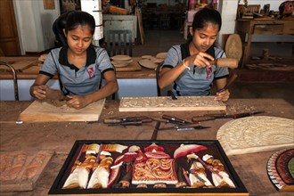 Native Sinhalese girls carving traditional wooden pictures
