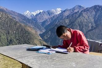 A schoolboy doing his homework outside