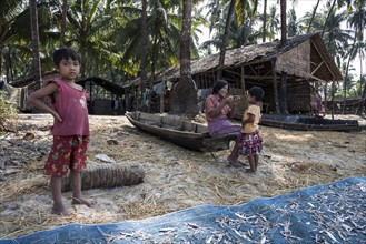 Native woman and two children in front of a wooden house of a fisherman on the beach