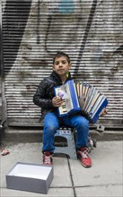 A boy playing the accordion on the road