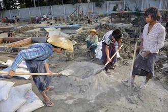 Children and teenagers mix concrete on a high rise construction site