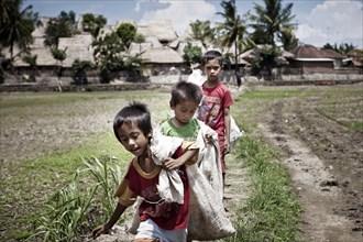 Indonesian children carrying sacks