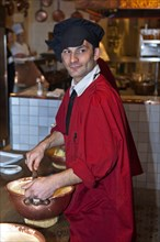 Chef preparing the traditional omelette mixture in copper bowls