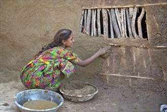 Girl in traditional dress plastering the wall of a house with a mixture of water