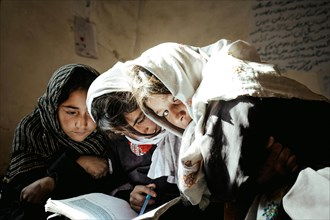 Three girls working with a textbook