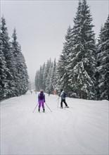 People skiing on the snowy slope of Bukovel ski resort in the Ukrainian Carpathian mountains. Snow falling scene