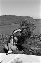 Gala et Dali posent sur la terrasse de la maison avec un dauphin ramené par les pêcheurs
