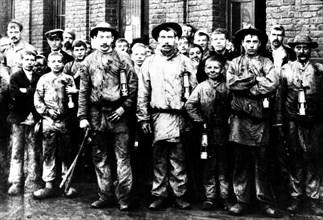 Groupe d'enfants et d'hommes travaillant dans la mine de Denain
