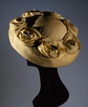 Yellow synthetic chiffon hat with flower appliqué in the same material with black pistils