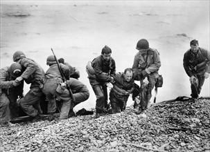 Soldats américains aidant leurs camarades à regagner le rivage sur une plage de Normandie (Juin 1944)