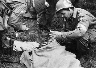 Un officier médical et un soldat allemand blessé (juin 1944)