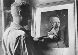 A GI looking at Hitler's portrait