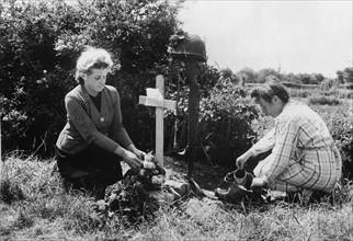 Deux habitantes de Carentan fleurissent la tombe d'un parachutiste américain