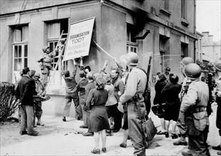 La population cherbourgeoise détruit l'insigne du bureau de l'Organisation Todt juste après la libération