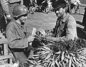 Sur le marché de Cherbourg, un soldat américain achète des légumes à un paysan normand