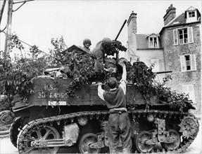 Un civil français donne un verre de vin à un équipage de char américain