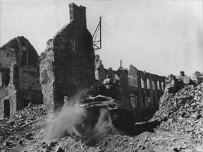 Un char Sherman M-4 américain traverse Périers dévasté, en direction de Coutances