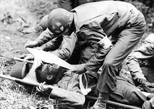 Un GI's blessé par un éclat de mortier allemand est soigné par un infirmier (1944)