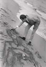 Bernard Buffet dessinant sur le sable