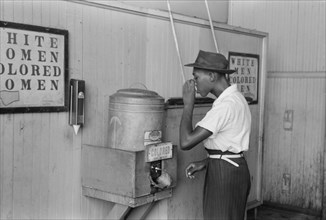 """Man Drinking Water at """"Colored"""" Water Cooler in Bus Terminal, Oklahoma City, Oklahoma, USA, Russell Lee, Farm Security Administration, July 1939"""