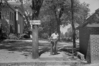 """Boy at Drinking Fountain with Sign """"Colored"""" on County Courthouse Lawn, Halifax, North Carolina, USA, John Vachon, Farm Security Administration, April 1938"""