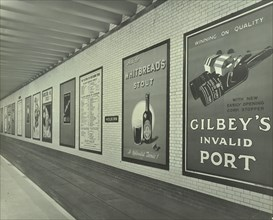 Advertisements for beer and port, Holborn Underground Tram Station, London, 1931. Artist: Unknown.