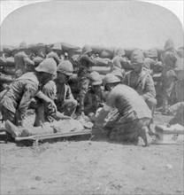 First aid to a wounded fusilier, Honey Nest Kloof Battle, Boer War, South Africa, February 1900.Artist: Underwood & Underwood