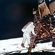 Edwin Buzz Aldrin descends the steps of the Lunar Module ladder to walk on the Moon, 1969.Artist: NASA
