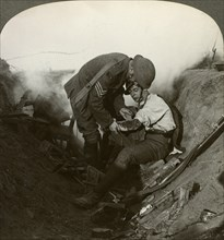 Soldier receiving first aid from a sergeant in a sap, Battle of Peronne, World War I, 1914-1918.Artist: Realistic Travels Publishers