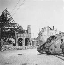 British tank in front of ruined buildings, Peronne, France, World War I, c1916-c1918. Artist: Nightingale & Co